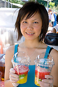 Teen SE Asian Hmong holding tiered cups of ice cold fruit drinks. Hmong Sports Festival McMurray Field St Paul Minnesota USA