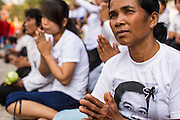 """01 FEBRUARY 2013 - PHNOM PENH, CAMBODIA:  A mourner wearing a tee shirt with the photo of former King Norodom Sihanouk on it, prays as the King's funeral procession passes her in Phnom Penh. Norodom Sihanouk (31 October 1922- 15 October 2012) was the King of Cambodia from 1941 to 1955 and again from 1993 to 2004. He was the effective ruler of Cambodia from 1953 to 1970. After his second abdication in 2004, he was given the honorific of """"The King-Father of Cambodia."""" Sihanouk died in Beijing, China, where he was receiving medical care, on Oct. 15, 2012. His cremation is will be on Feb. 4, 2013. Over a million people are expected to attend the service.   PHOTO BY JACK KURTZ"""
