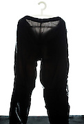 black raincoat pants on a plastic coathanger