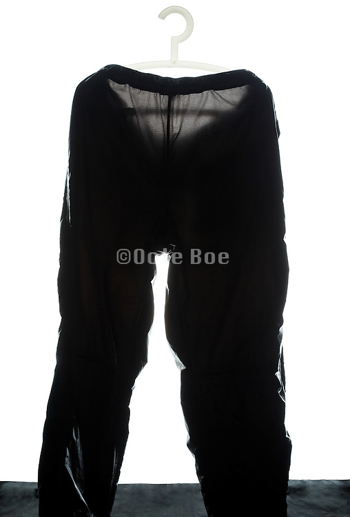 black raincoat pants on a plastic coathanger