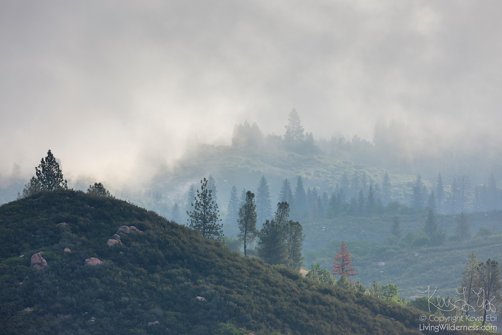 Thick clouds and fog blow over a ridge high above the South Fork of the Tuolumne River in the Stanislaus National Forest, California. This image was captured from a vista point known as the Rim of the World and is located west of Yosemite National Park.