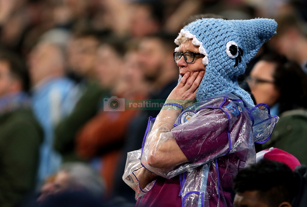 A Manchester City fan wearing a knitted hat