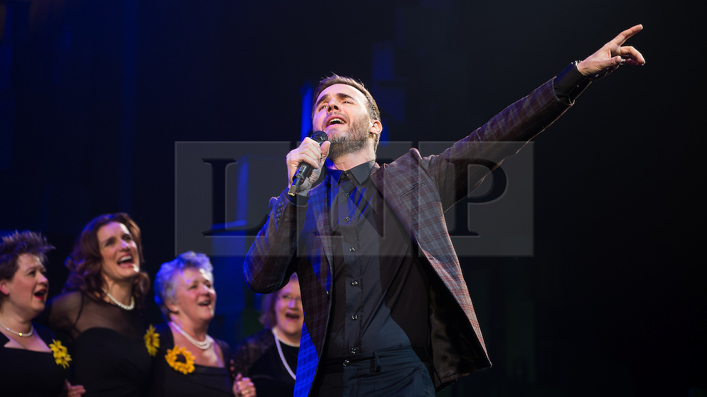 """© Licensed to London News Pictures . 12/01/2016 . Salford , UK . GARY BARLOW (pictured with the original Women's Institute members who made the calendar ) makes a surprise appearance and performs in front of the audience at the Lowry Theatre , during the opening week of """" The Girls """" , a musical he wrote based on the story """" Calendar Girls """" , about a group of Women's Institute members in Yorkshire , who made a nude calendar . Photo credit : Joel Goodman/LNP"""
