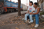 25 OCTOBER 2003 -- TAPACHULA, CHIAPAS, MEXICO:  A couple for Honduras waits in the train yards in the Mexican town of Tapachula, hoping to hop the freight trains north on their way to the US. Tapachula is center of the smuggling industry between Mexico and Guatemala. Consumer goods are smuggled south to Guatemala (to avoid paying Guatemalan import duties) and people are smuggled north into Mexico. Most of the people coming north are hoping to eventually get to the United States. PHOTO BY JACK KURTZ