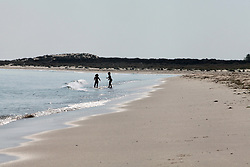 Covid 19 - Two children play on the usually packed beach owned by  the National Trust at Shell Bay Dorset. Normally very busy with visitors now empty and closed due to coronavirus, UK April 2020