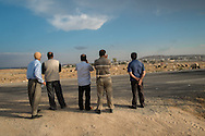 Syrians Kurdish men watch smoke coming from their hometown of Kobane/Ayn al-Arab (background right) from the Turkish side of the border near Suruç.