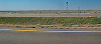 a lonely windmill stands along interstate 20 in rural flat west Texas panorama