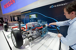 Visitor using plug-in electric charging station for Nissan vehicle at Paris Motor Show 2010
