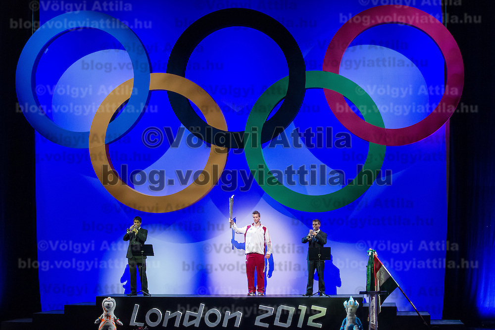 Highschool student and sportsman Laszlo Sari (C) holds the Olympic torch during a swearing in ceremony of the Hungarian Olympic Team that will travel to London in Budapest, Hungary on June 22, 2012. ATTILA VOLGYI