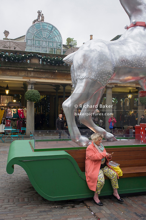 Awkward-looking Christmas theme stag legs and shopper sitting on bench.