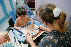Child and teacher doing a jigsaw together at a centre for rehabilitation and education for children with disabilities; in Havana Cuba,