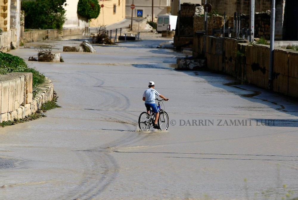 A boy cycles through waning flood waters in Qormi, outside Valletta, October 25, 2010.  An overnight storm dumped 87.3mm of rainfall on the Mediterranean island of Malta, causing some damage but no casualties, according to government officials...REUTERS/Darrin Zammit Lupi (MALTA)