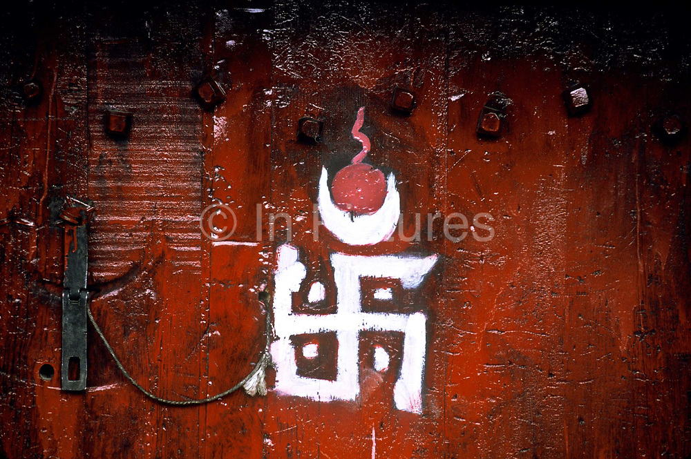 The red painted doors of private homes with the emblems of the Sun and Moon represent the Dalai and Panchen Lamas.