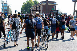 People make their way to the carnival on Ladbroke Grove, having to pass through metal detectors and a possible search as day one, Children's Day, of the Notting Hill Carnival gets underway in London. London, August 25 2019.