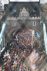 © Licensed to London News Pictures. 23/04/2017. LONDON, UK.  Crowds of marathon runners cross Tower Bridge, seen from the glass walkway of Tower Bridge, as runners reach the half way point.  Photo credit: Vickie Flores/LNP