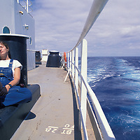 USA, Alaska, Second mate Karen Devine naps in summer sun aboard Oil tanker Arco Juneau sailing for San Francisco, CA