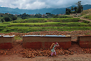 Nirmala Pahari, 40, carries bricks as other workers rebuild a wall around a brick kiln outside Kathmandu, Nepal. The mother of three works most of the year at the kiln, earning between $3 and $7 each day. Women kiln workers typically earn two-thirds less per day than their male counterparts.