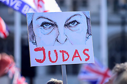 © Licensed to London News Pictures. 29/03/2019. LONDON, UK. A sign, depicting Theresa May as Judas, held up by a Pro-Leave supporter attending a rally in Parliament Square on the day that the UK was due to leave the European Union. MPs have just voted against supporting Prime Minister Theresa May's Withdrawal Agreement for a third time.  Photo credit: Stephen Chung/LNP