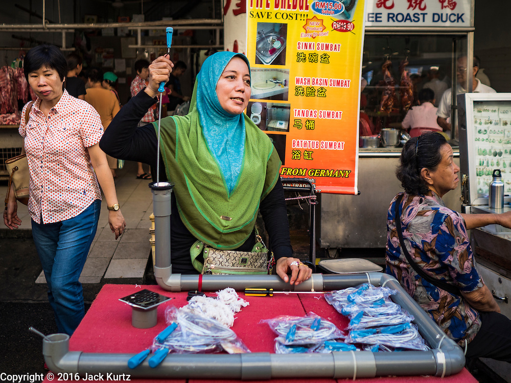 17 NOVEMBER 2016 - GEORGE TOWN, PENANG, MALAYSIA:  A Muslim woman sells plumbing supplies in a market in George Town, Penang, Malaysia. George Town is a UNESCO World Heritage city and wrestles with maintaining its traditional lifestyle and mass tourism.       PHOTO BY JACK KURTZ