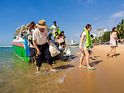 06 JANUARY 2015 - PATTAYA, CHONBURI, THAILAND:  Chinese tourists get off a rented speedboat after a tour of Pattaya beach. The Thai government has announced plans to clean up Pattaya beach, one of the most famous beaches in Thailand. Pattaya is about 2.5 hours from Bangkok. They plan to reduce the number of umbrella and chaise lounge vendors on the beach and regulate the personal watercraft and parasailing vendors on the beach. The government has already cleaned up beaches on Phuket island and Hua Hin.   PHOTO BY JACK KURTZ