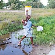 CAPTION: Selina collects water from a stream near the village of Mawoneke. While this water is understood by its users to be safe to drink owing to the proximity to its source, it tastes brackish and is widely disliked. Villagers tend to have to travel far with heavy buckets in order to bring water for household and agricultural use. The Bindagombe Irrigation Scheme will provide them with more borehole water access points, considerably reducing travel time and the corresponding effort that must be expended. LOCATION: Mawoneke Village, Chivi District, Masvingo Province, Zimbabwe. INDIVIDUAL(S) PHOTOGRAPHED: Tavonga Chinheva (left) and Selina Chiwaka (right).