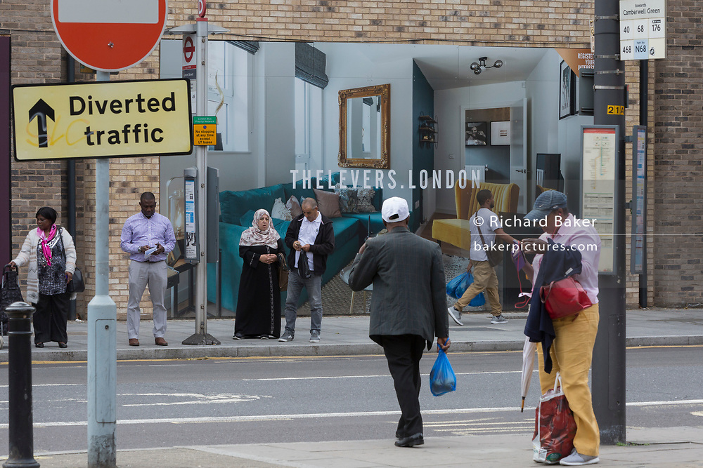 Local Londoners await the next bus in front of a marketing billboard for The Levers - a new apartment development on the Walworth Road at Elephant And castle, on 4th September 2018, in Southwark, London, England. The Levers (A Peabody development) will be a complex of 1,2,and 3 bed flats close to Elephant & Castle and Elephant Park - both undergoing major redevelopment.