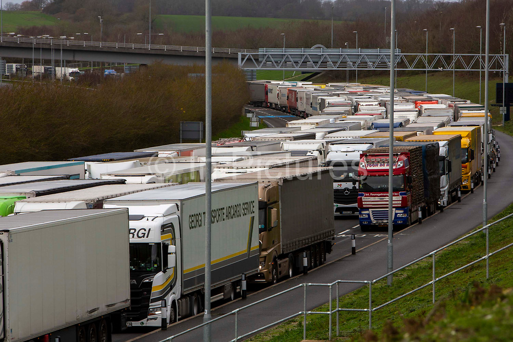 Lorries line up due to customs delays at the entrance of the Eurotunnel, Cheriton, Folkestone, Kent. United Kingdom on the 18th of December 2020. The Channel Tunnel is a 50.45-kilometre rail tunnel linking Folkestone, Kent, in the United Kingdom, with Coquelles, Pas-de-Calais, near Calais in northern France, beneath the English Channel.