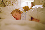 Young boy sleeping in a hotel bed, Devon, England