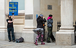 """© Licensed to London News Pictures; FILE PICTURE 22/06/2021; Bristol, UK. YASMIN SCHNEIDER (with pink hair) walks past a man with a placard outside Bristol Crown Court. Yasmin Schneider is charged with two counts of outraging public decency and is one of the defendants facing charges related to a """"Kill the Bill"""" protest and riot against the Police, Crime, Sentencing and Courts Bill. During the protest on 21 March 2021 two police vehicles were burnt out and windows on Bridewell Police Station were smashed. The Police, Crime, Sentencing and Courts Bill proposes new restrictions on protests. Photo credit: LNP."""