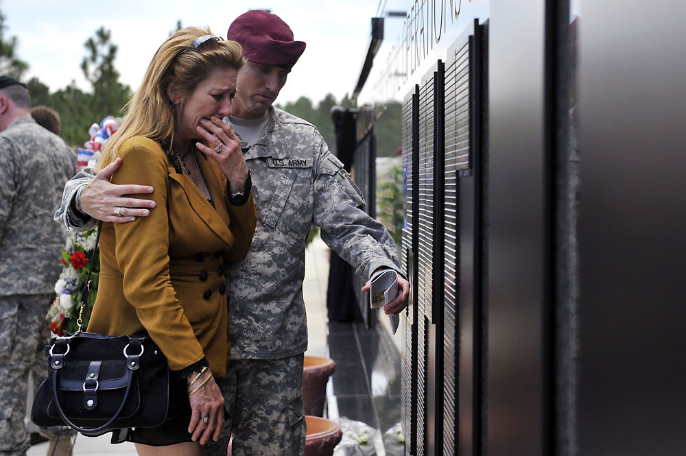 Lisandra Metzger is comforted by a soldier who points out the name of her son, Sergeant First Class David Metzger. Sergeant Metzger died on October 26, 2009 while on duty in Afghanistan.  A new memorial wall for USASOC was unveiled on Thursday, May 27, 2010.   Thirty five names were added to the wall, bringing the total to over 1,000 names.
