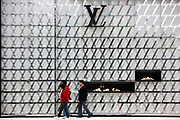 Pedestrians walk past a large Louis Vuitton display outside a high-end shopping mall in Shanghai, China, on October 01, 2011. China is by far the world's fastest growing market for luxury brands.