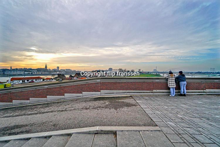Nederland, Nijmegen, 10-12-2020  Tijdens de aanleg van de nevengeul in de waal is vastgelegd dat op het daardoor ontstane eiland veurlent in een strook tussen de oude waalbrug en de brug de lentloper , tegenover de oude bebouwing, woningbouw zou plaatsvinden. Na voltooing van het rivierpark bleek het eiland een oase van rust en recreatie te worden van met name de vinexwijk nijmegen-noord. Nu willen veel nijmegenaren dat de geplande woningbouw geschrapt wordt en het hele eiland voor recreatie te gebruiken. Het stuk wat verderop naar de spoorbrug loopt en daarachter is lager waardoor daar niet gebouw kan worden en is een gewild gebied voor wandelaars. Ook lopen er schotse hooglanders, wilde runderen, rond .Foto: ANP/ Hollandse Hoogte/ Flip Franssen