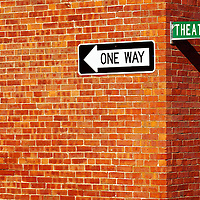 Street direction and street name signage attached to a classic New England red brick wall.