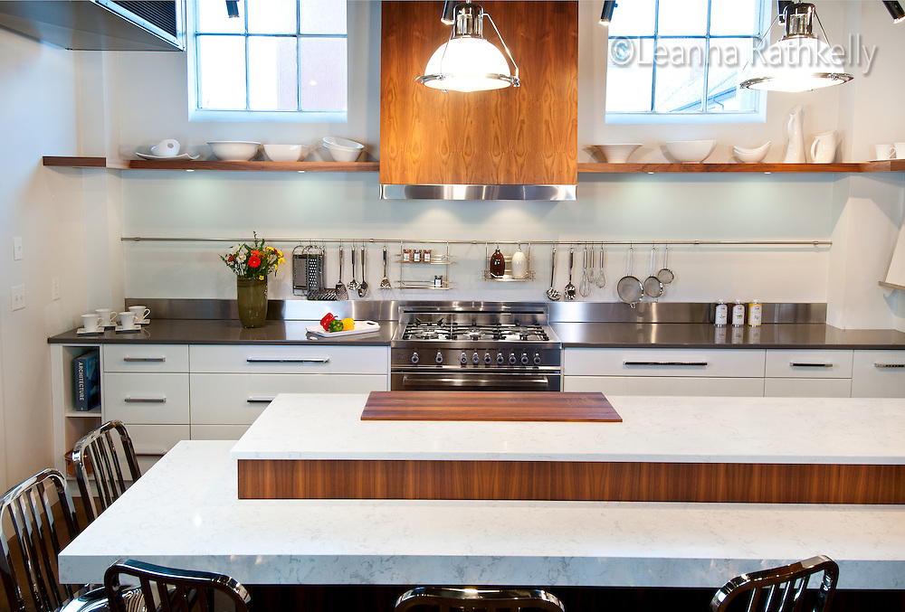 A contemporary kitchen in Urbana Kitchens showroom in Victoria, BC features bookended walnut on the hood fan cover, white Cambria quartz counters and a stainless Bertuzzi gas range.