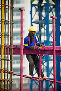 22 FEBRUARY 2013 - BANGKOK, THAILAND: Workers on the scaffolding at the Bhiraj Tower construction site. The Bhiraj Tower is new mixed use residential/office/retail complex under construction on Sukhmvit Road at Soi 33, across the street from the Emporium, a high end retail center. The Bhiraj should be finished in 2014 and will be 45 stories tall.       PHOTO BY JACK KURTZ