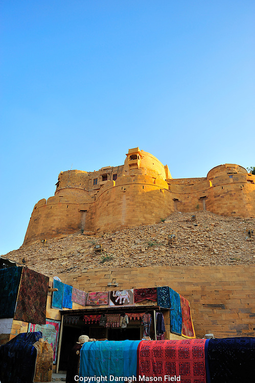 Jaisalmer fort in Rjasthan, in the Golden City. Merchant carpets are in the foreground