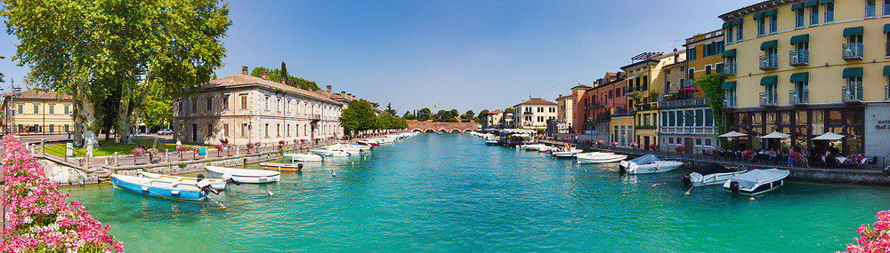 Panoramic view of the water channel of the Peschiera del Garda village on Lake Garda, Italy with boats anchored along the canal and businesses and restaurants with people during a sunny summer afternoon