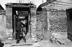 Man pushing bicycle into old house in hutong in Beijing China