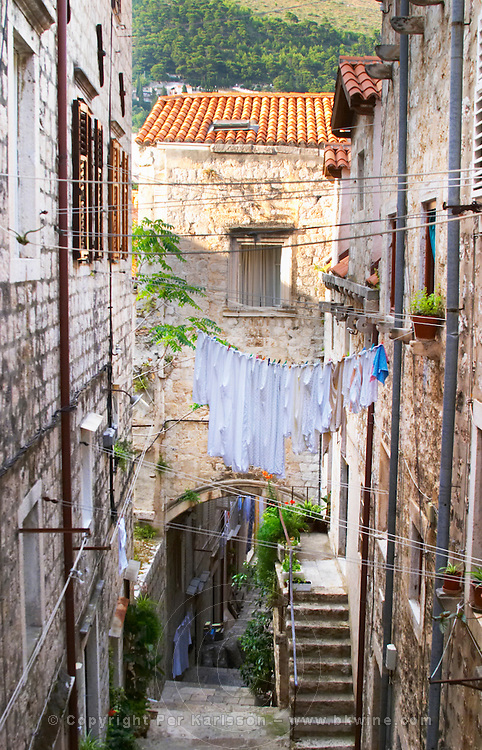 A narrow street leading down with steep steps, clothes lines hanging across the street, clothes hanging to dry Dubrovnik, old city. Dalmatian Coast, Croatia, Europe.