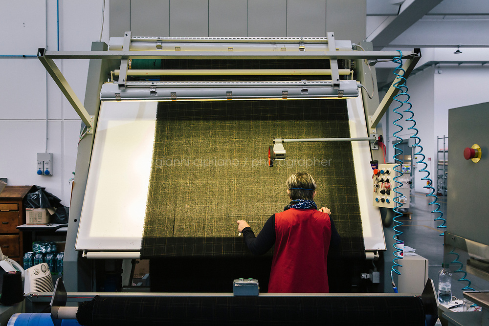"""PRATO, ITALY - 25 NOVEMBER 2019: Carmela D'Ambrosio (56) is seen here checking the quality of a fabric at Marini Industrie, a textile company that has survived Chinese competition in Prato, Italy, on November 25th 2019. Carmela D'Ambrosio  has been working at Marini Industrie for 20 years. Marini Industrie is one of the few companies in Prato that weren't hit by Chinese competition, by elevating their quality.<br /> <br /> Italy has proved especially vulnerable to China's emergence as a manufacturing juggernaut, given that many of its artisanal trades -- textiles, leather, shoe-making -- have long been dominated by small, family-run businesses that lacked the scale to compete on price with factories in a nation of 1.4 billion people. <br /> In recent years, four Italian regions that were as late as the 1980s electing Communists and then reliably supported center-left candidates -- Tuscany, Umbria, Marche and Emilia-Romagna  -- have swung dramatically to the extreme right. Many working class people say that delineation has it backwards: The left abandoned them, not the other way around. <br /> <br /> Between 2001 and 2011, Prato's 6,000 textile companies shrunk to 3,000, and those employed by the plants plunged from 40,000 to 19,000, according to Confindustria, the leading Italian industrial trade association. As Prato's factories went dark, people began arriving from China - mostly from the coastal city of Wenzhou, famed for its industriousness - to exploit an opportunity.<br /> They set up sewing machines across the concrete floors and imported fabric from factories in China. They sewed clothes, cannily imitating the styles of Italian fashion brands. They affixed a valuable label to their creations: """"Made In Italy""""."""