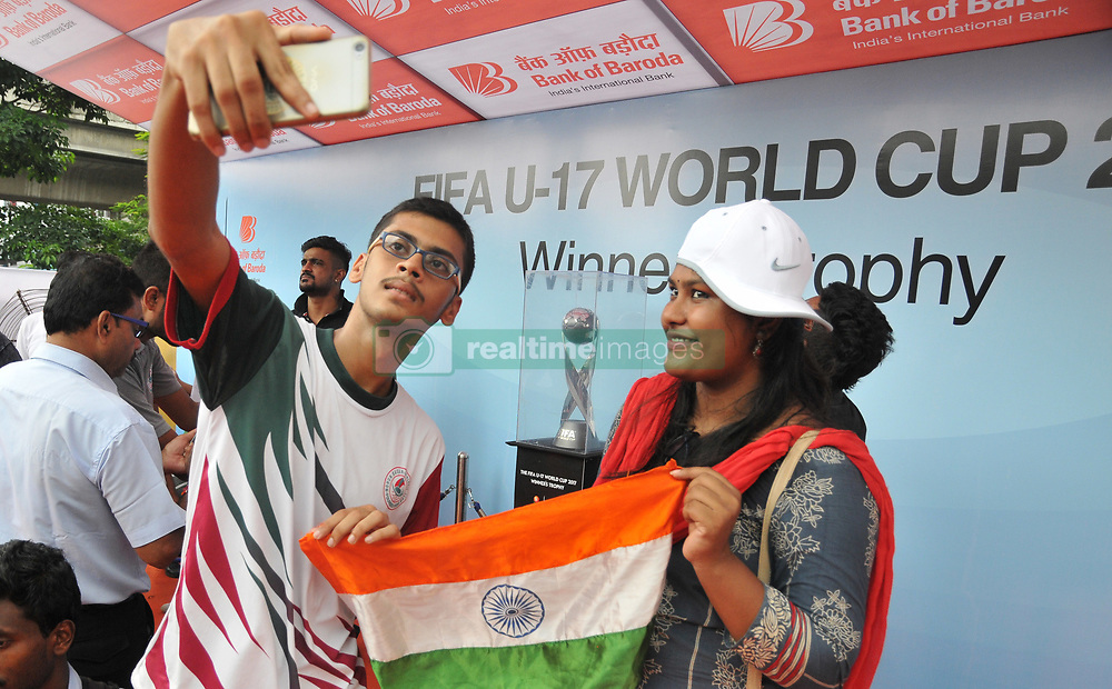 "August 30, 2017 - Kolkata, West Bengal, India - India Sports lovers hold Indian National Flag and his mobile camera Selfie at  The FIFA U17 World Cup 2017 Winners Trophy visit in Kolkata City  on August 30,2017 in India...The trophy tour will cover almost 9,000 km over a period of 40 days between August 17 and September 26.....Fans will be able to see the trophy in the six host cities starting with New Delhi, where India will be playing their group matches. The silverware will be on display in the capital city from August 17 to 22.....Guwahati will be next stop August 24-29 followed by Kolkata, which will host the final, between August 31 to September 5.  Fans in Mumbai will get to set their sight on the trophy between September 6 and 10, while it is scheduled to be on view in Goa from September 14 to 19.....The final destination will be Kochi where the trophy will reside from September 21 till 26.....Describing the event, Chairman of the LOC Praful Patel said: ""The Trophy Experience will mark the last phase of our event promotion and it is very important, because it will give the fans around the country the opportunity to get up close to the same Official Winner's Trophy that the captain of the winning team of the FIFA U-17 World Cup will be lifting on October 28 in Kolkata.....""This is a once-in-a-lifetime chance and we hope that people can come in large numbers to the display locations in the host cities.""....""This initiative is about bringing the excitement of the FIFA U-17 World Cup Trophy Experience closer to India's fans in the run up to this milestone competition,"" said FIFA Chief Commercial Officer Philippe Le Floc'h.....""The trophy embodies both the dreams of the best U-17 players in the world and those of millions of Indian fans who will be hosting the football World Cup in October,"" he added.....The FIFA"