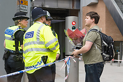 London, June 4th 2017. A man with flowers speaks to police officers during a massive policing operation in the aftermath of the terror attack on London Bridge and Borough Market on the night of June 3rd which left seven people dead and dozens injured