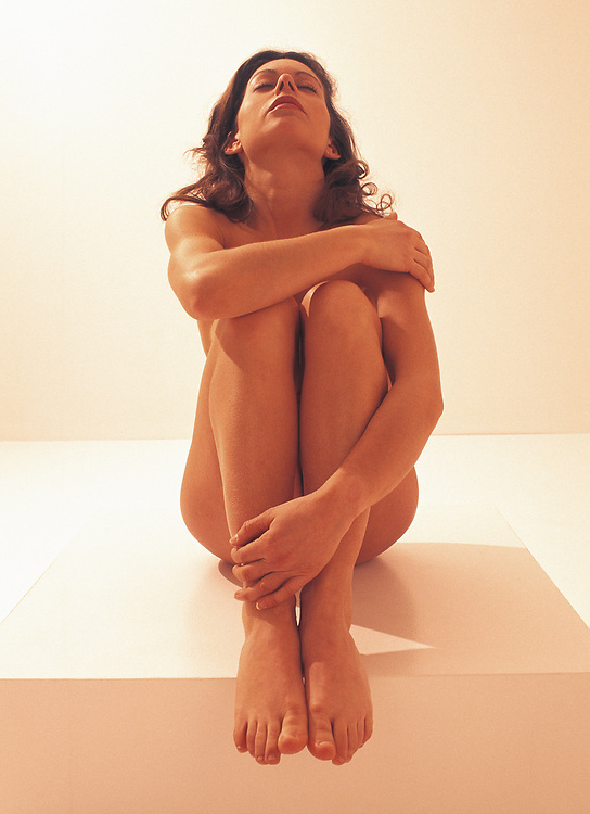 A nude woman sitting on platform with arms around legs and head thrown back with rich warm light hitting her