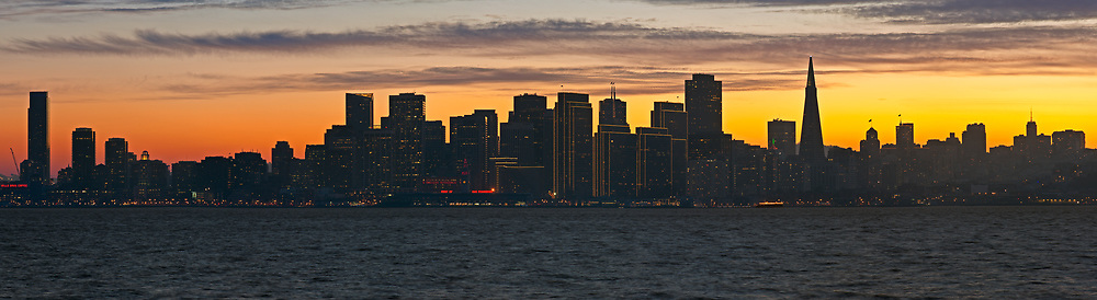 The San Francisco skyline is seen silhouetted by the setting sun. As seen from Treasure Island. San Francisco, California.