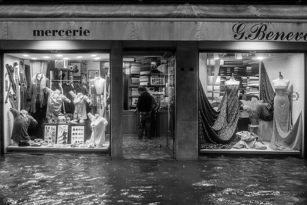 Venice, Italy. 29 October, 2018.  Workers check the water level inside their shop during the high tide in San Marco district on October 29, 2018, in Venice, Italy. This is a selection of pictures of different areas of Venice that the press has not covered, were resident live and every year they have to struggle with the high tide. Due to the exceptional level of the 'acqua alta' or 'High Tide' that reached 156 cm today, Venetian schools and hospitals were closed by the authorities, and citizens were advised against leaving their homes. This level of High Tide has been reached in 1979. © Simone Padovani / Awakening / Alamy Live News