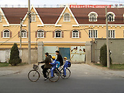 family on bicycle passing a new residential building complex under construction
