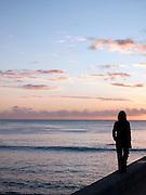 Woman walks along a sea wall near Waikiki Beach at Honolulu, O'Ahu, Hawai?i