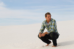man on a sand dune in White Sands New Mexico