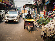 07 MARCH 2014 - MAE SOT, TAK, THAILAND:  A mango vendor pushes his cart through the Burmese market section of Mae Sot, Thailand.    PHOTO BY JACK KURTZ