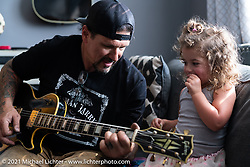 Billy Lane takes a guitar break while his family visit him above his new shop in Columbia, TN after moving from Florida. Monday, May 24, 2021. Photography ©2021 Michael Lichter.